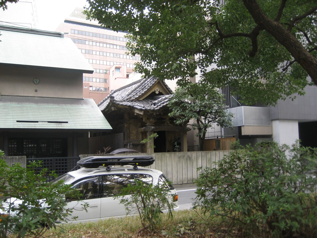 a small, wooden, old-style, Japanese building (the type with the roof that curves upward at the tips) that was sandwiched between a modern apartment complex and a modern office building.